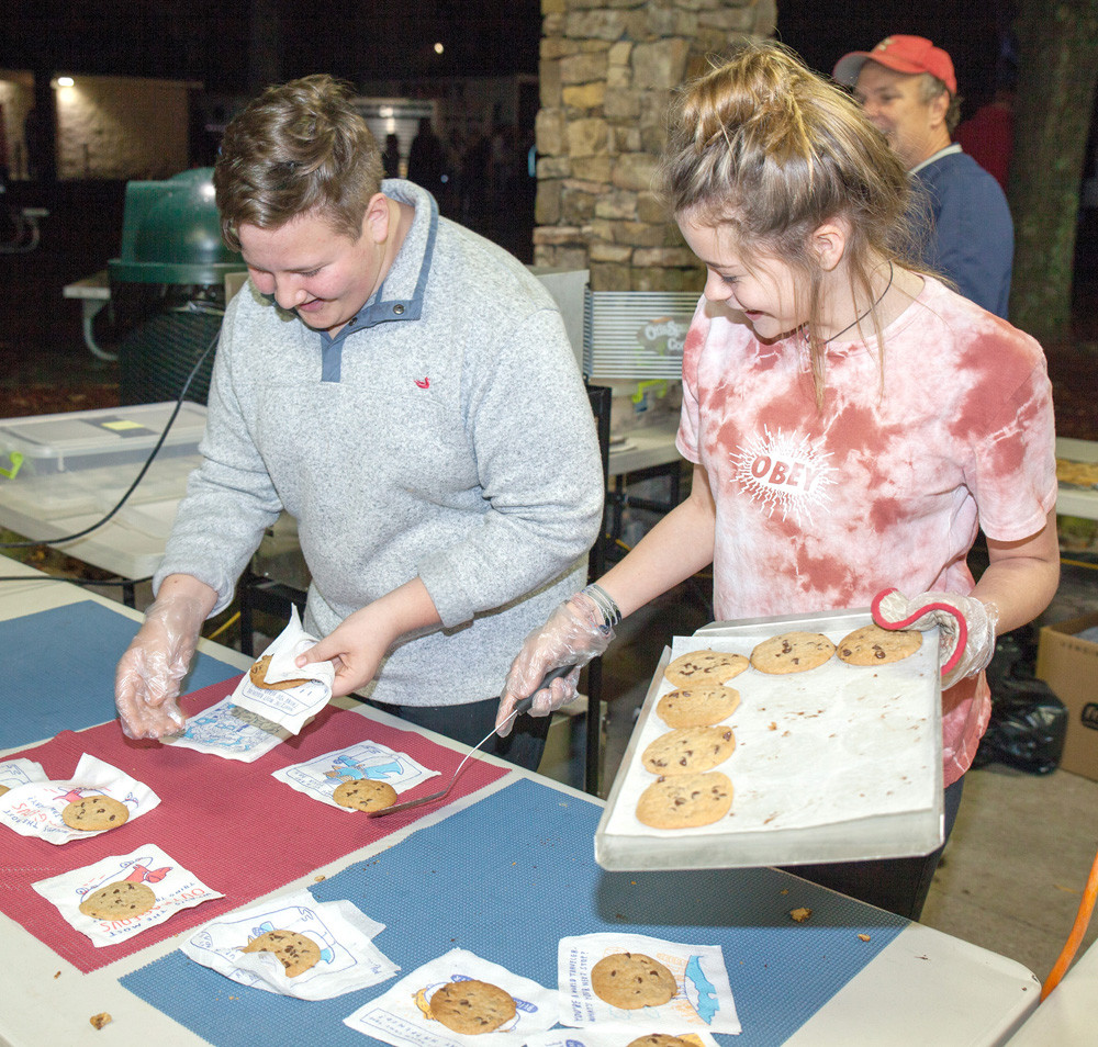 AT THE END of the living nativity, attendees were given tickets to visit the Greenway Pavilion to enjoy free hot chocolate and freshly baked cookies.  Jaxson Munck, left, and Mady Price keep the cookie table stocked during the event on Thursday night.