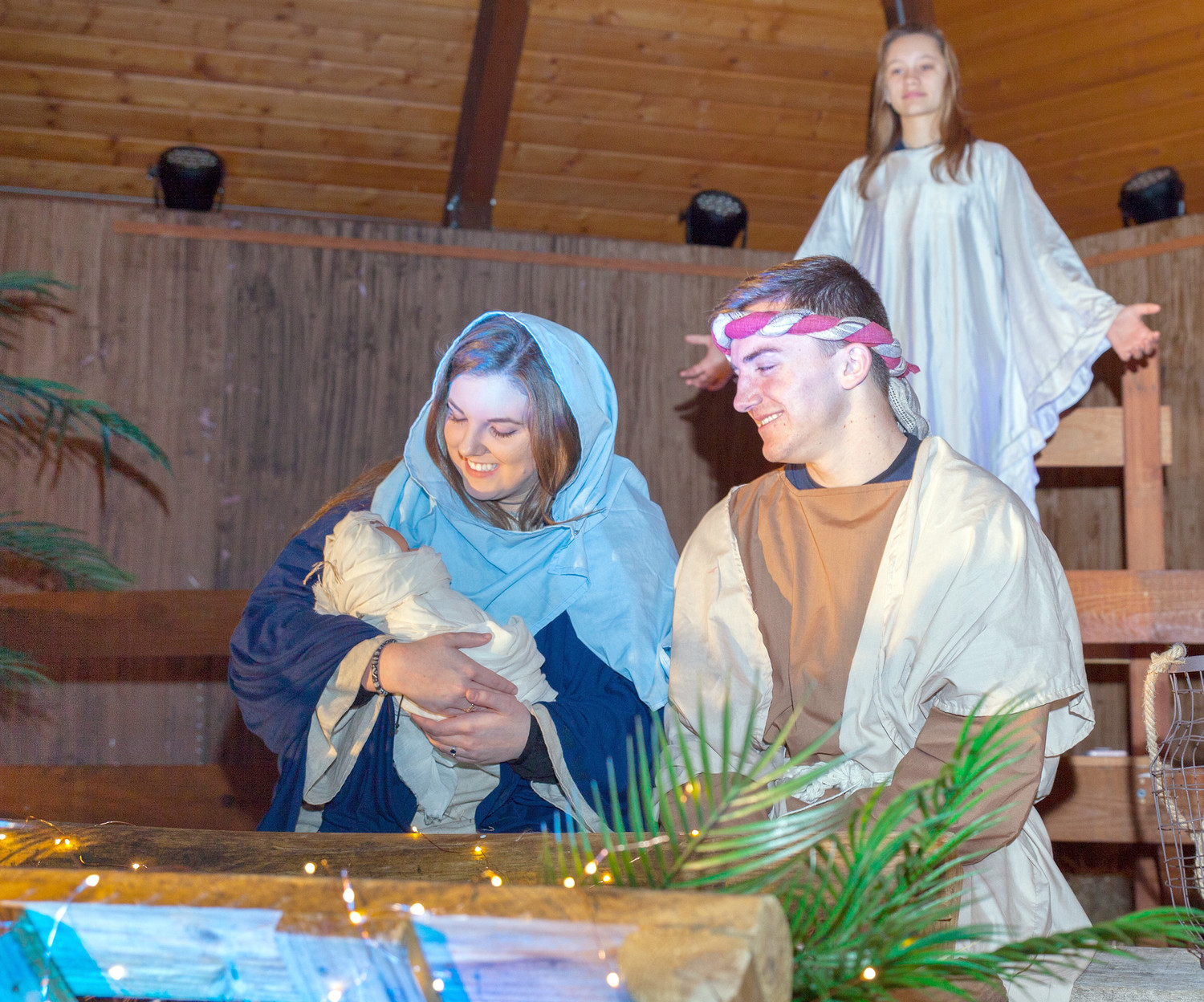 MARY AND JOSEPH, pictured above, hold the newly born baby Jesus in the stable as an angel appears behind them. The live nativity story was presented Thursday night at the Greenway Park near the Pavilion and will be repeated tonight and Sunday night. At left, three shepherds watch their flock at night during the live nativity story.