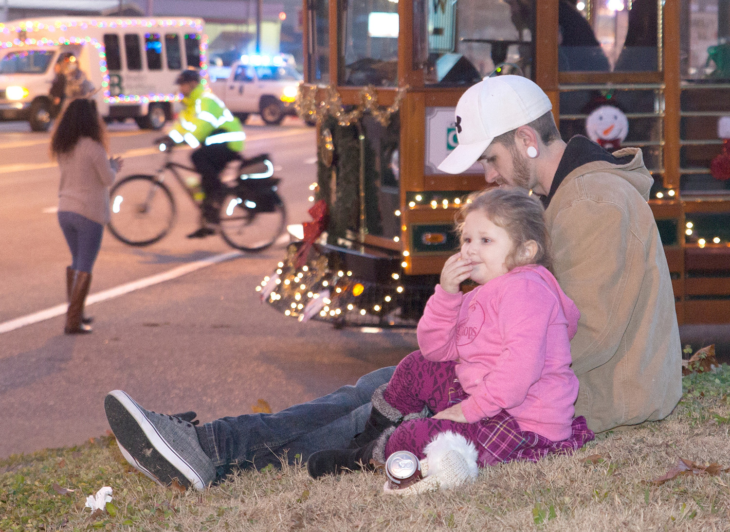 A FATHER AND DAUGHTER enjoy the beginning of the Mainstreet Cleveland Christmas Parade on Saturday night.