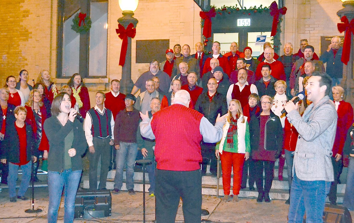 TATUM BRINKMAN, left, and Dr. Tyler Brinson sing a Christmas duet at the lighting of the downtown holiday tree Friday.