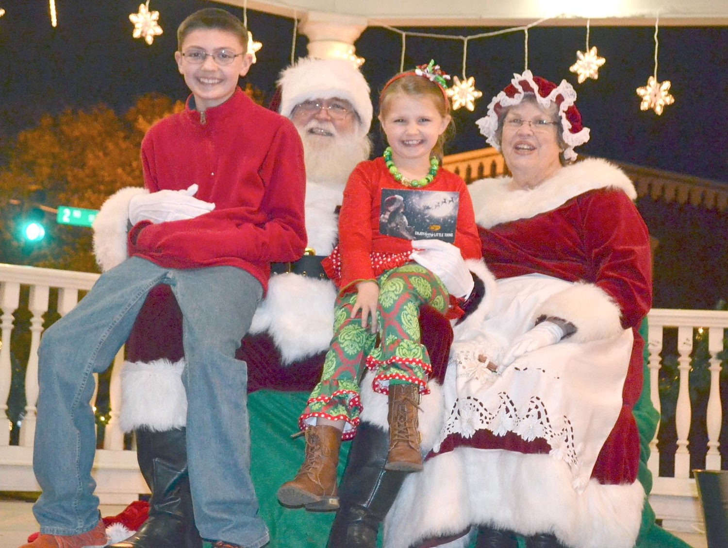 SANTA AND MRS. CLAUS took time for photographs with children at Friday's Christmas tree lighting. With the couple are 12-year-old Davian Voyles, and his sister, 6-year-old Ayda.