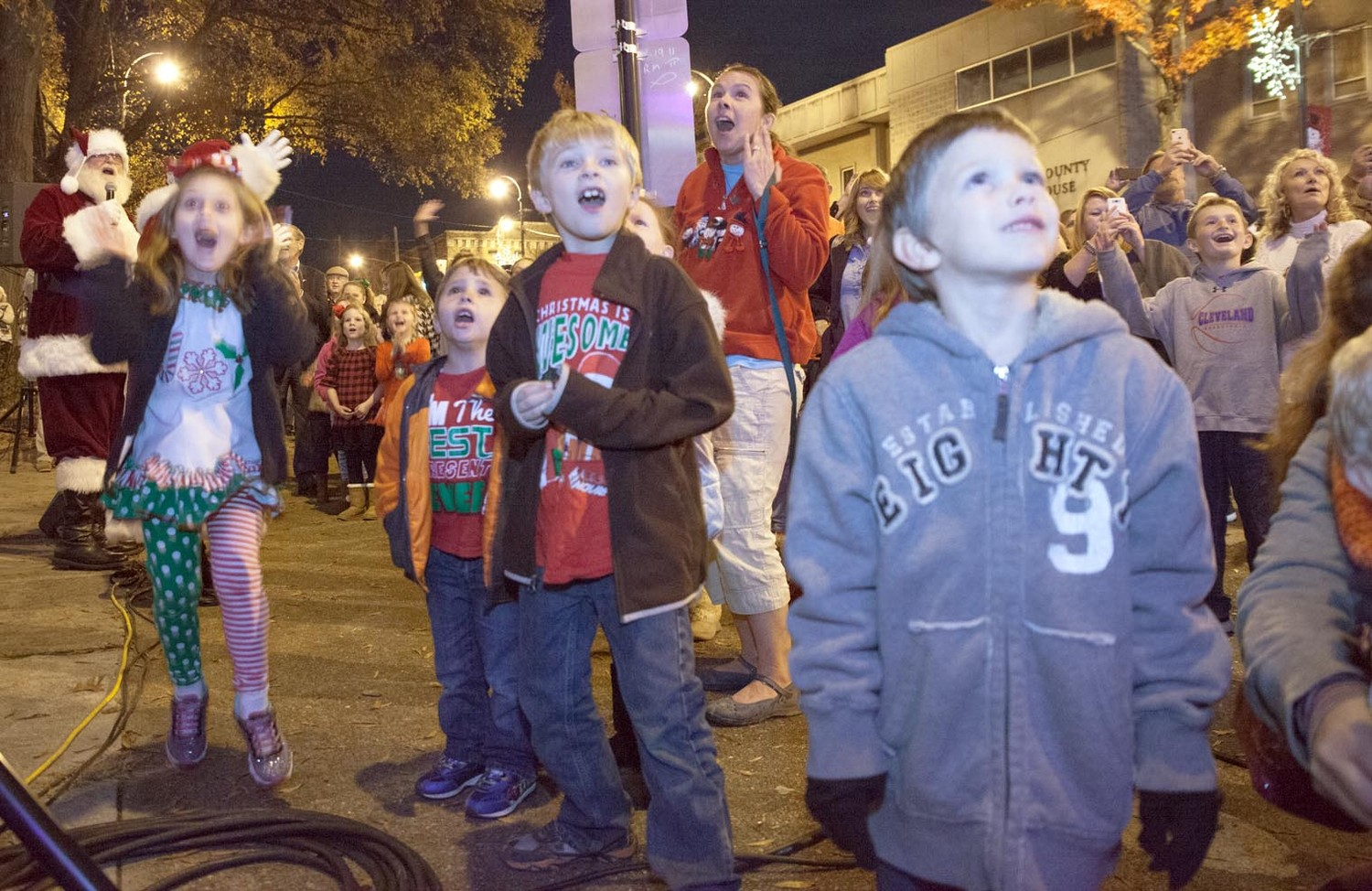 "AN ANXIOUS GROUP of kids react in amazement as the Christmas Tree lights spring to life during the Friday night ceremony as Santa belts out ""Merry Christmas!  Ho ho ho!""  The tree-lighting ceremony was prefaced by carols sung by the First Baptist choir and was bookended by pictures with Santa in the Bandstand at Courthouse Plaza, free downtown carriage rides, and reverse caroling at downtown area churches."