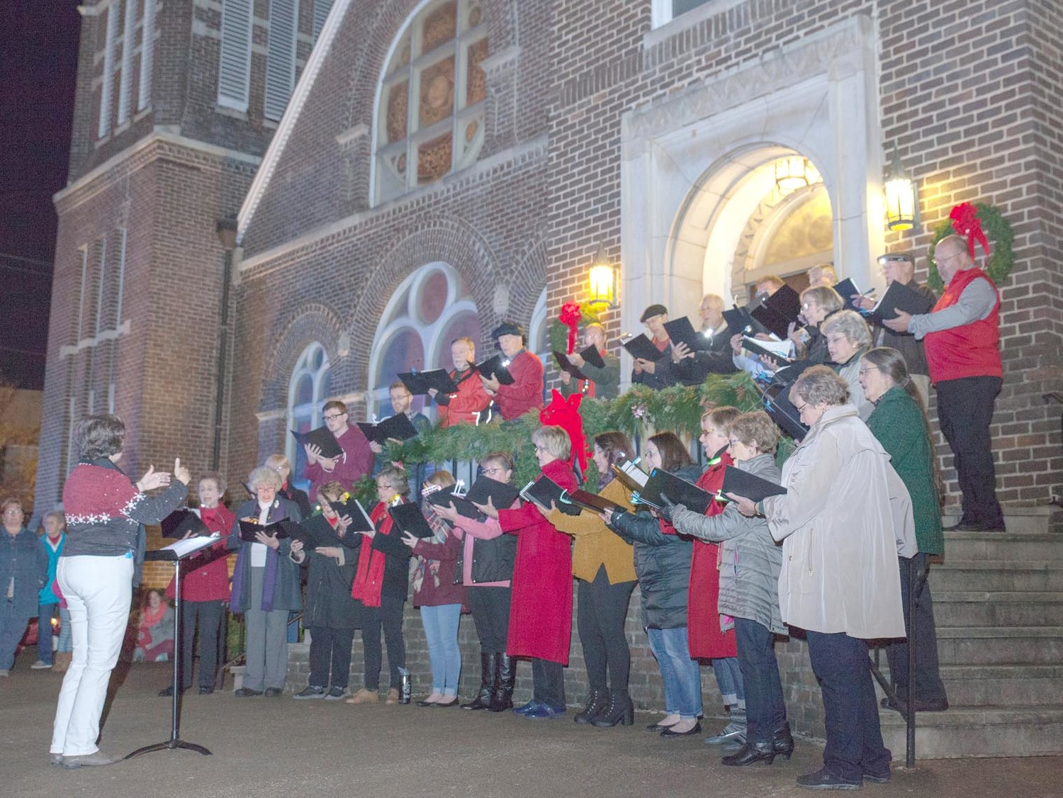 AT THE FIRST STOP on the reverse caroling tour, the Broad Street United Methodist Church choir treats the crowd to some Christmas carols.
