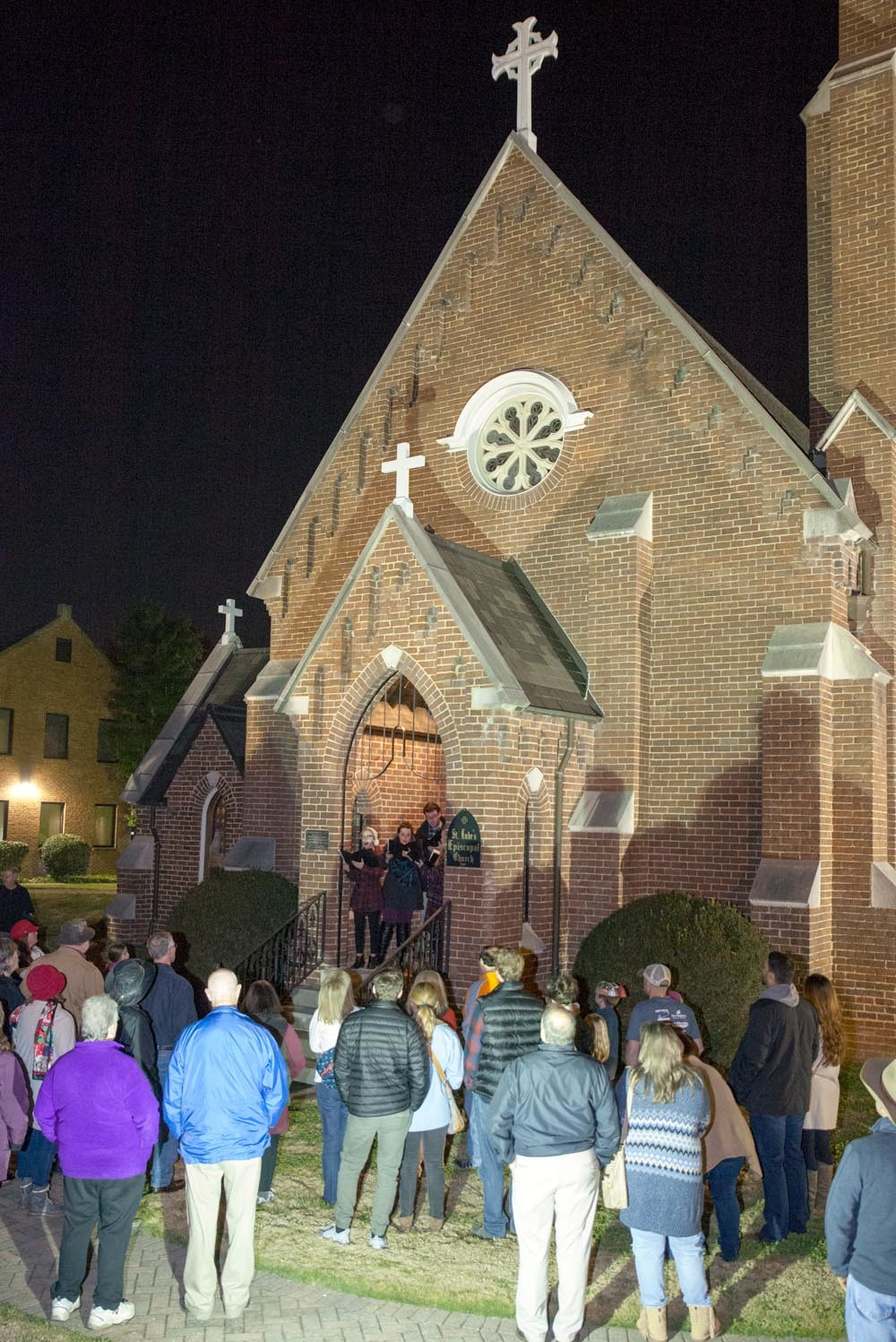 THE DOWNTOWN CHRISTMAS Tree Lighting attendees surround the entryway of St. Luke's Episcopal Church to listen to more carols.
