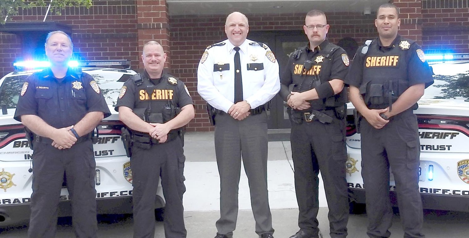 BRADLEY COUNTY SHERIFF'S OFFICE deputies stand in front of vehicles that will now be allowed to drive and monitor workshop centers, With some of the patrol cars are, from left, Deputy James Dearth, Deputy Jay Lawson, Sheriff Eric Watson, Deputy David Harper,and Deputy Marlon Nelson.