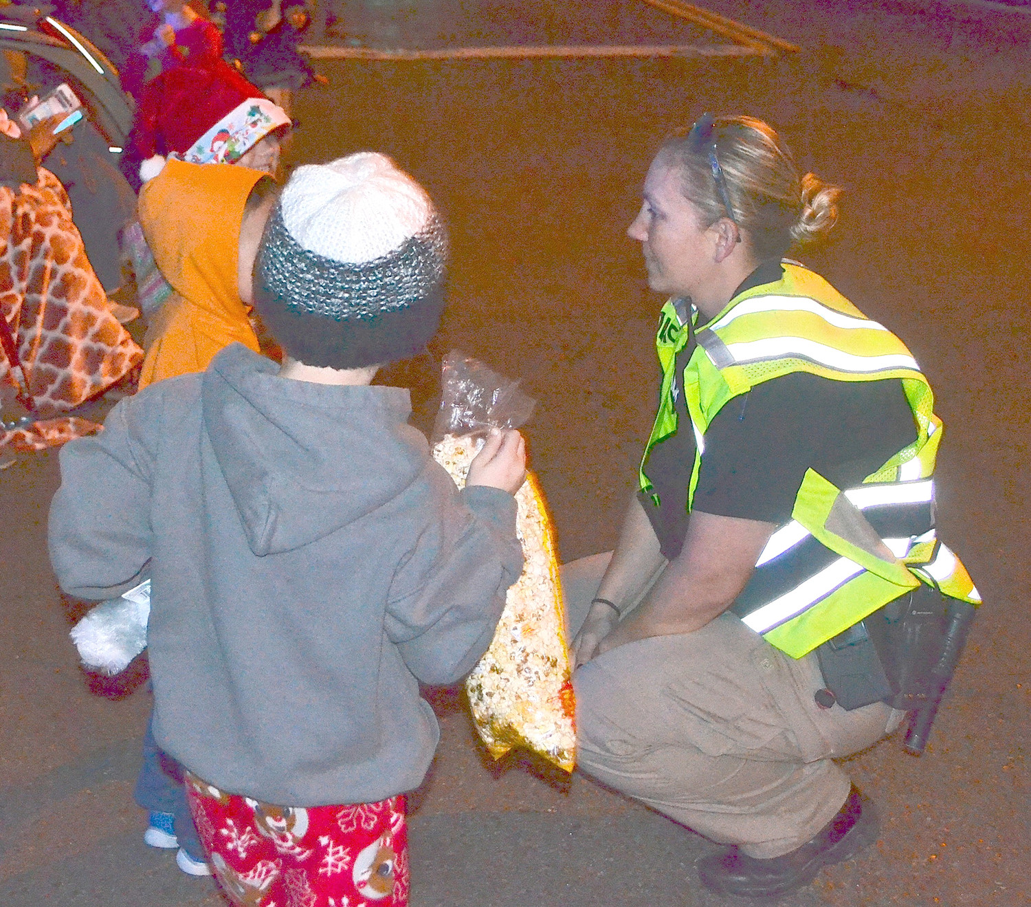 CLEVELAND POLICE OFFICER Jennifer Samples talks to several children who were anticipating the arrival of Santa , the bands, floats and candy.