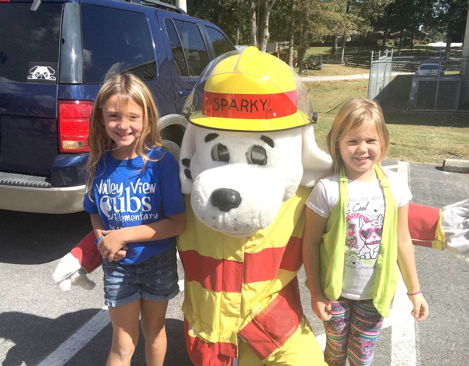 VALLEY VIEW Elementary School students Nevaeh Longwell and Gabby Mason pose with Bradley County Fire-Rescue mascot Sparky during his visit to the school.