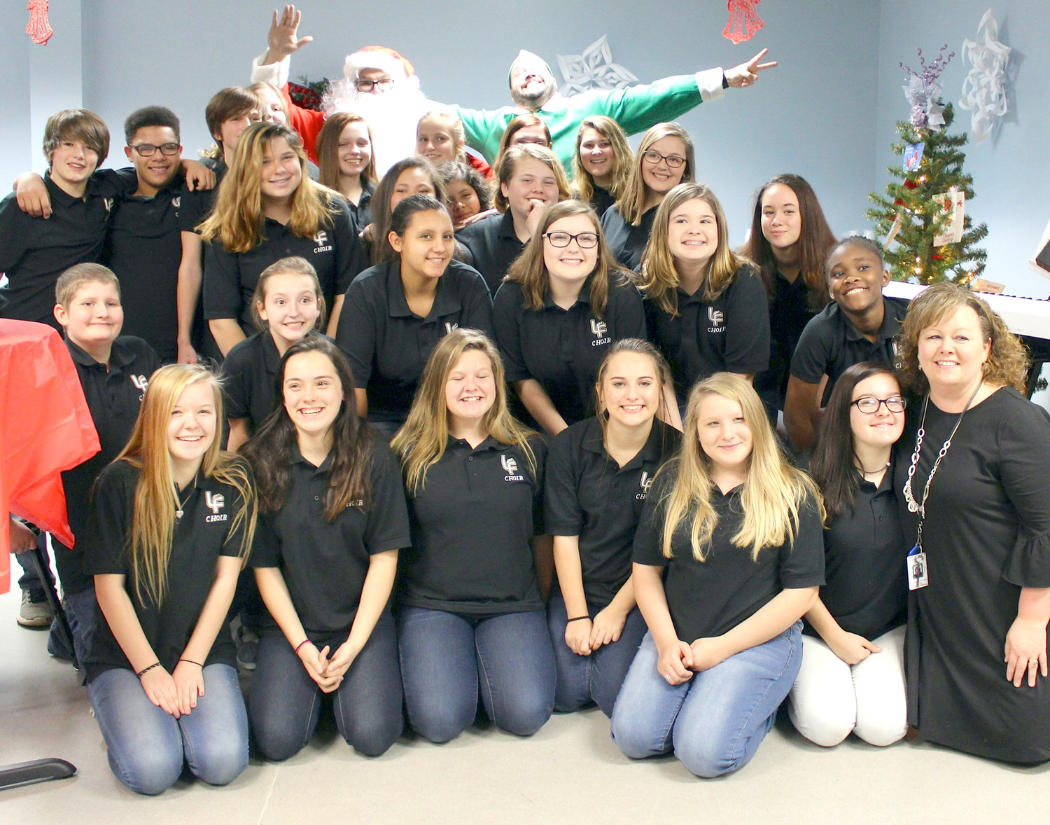 "STUDENTS in Lake Forest Middle School's Revolution show choir sang during the ""Holidays for Heroes"" party at the Whirlpool Customer eXperience Center. They are joined here by Santa Claus, Buddy the Elf and their leaders."