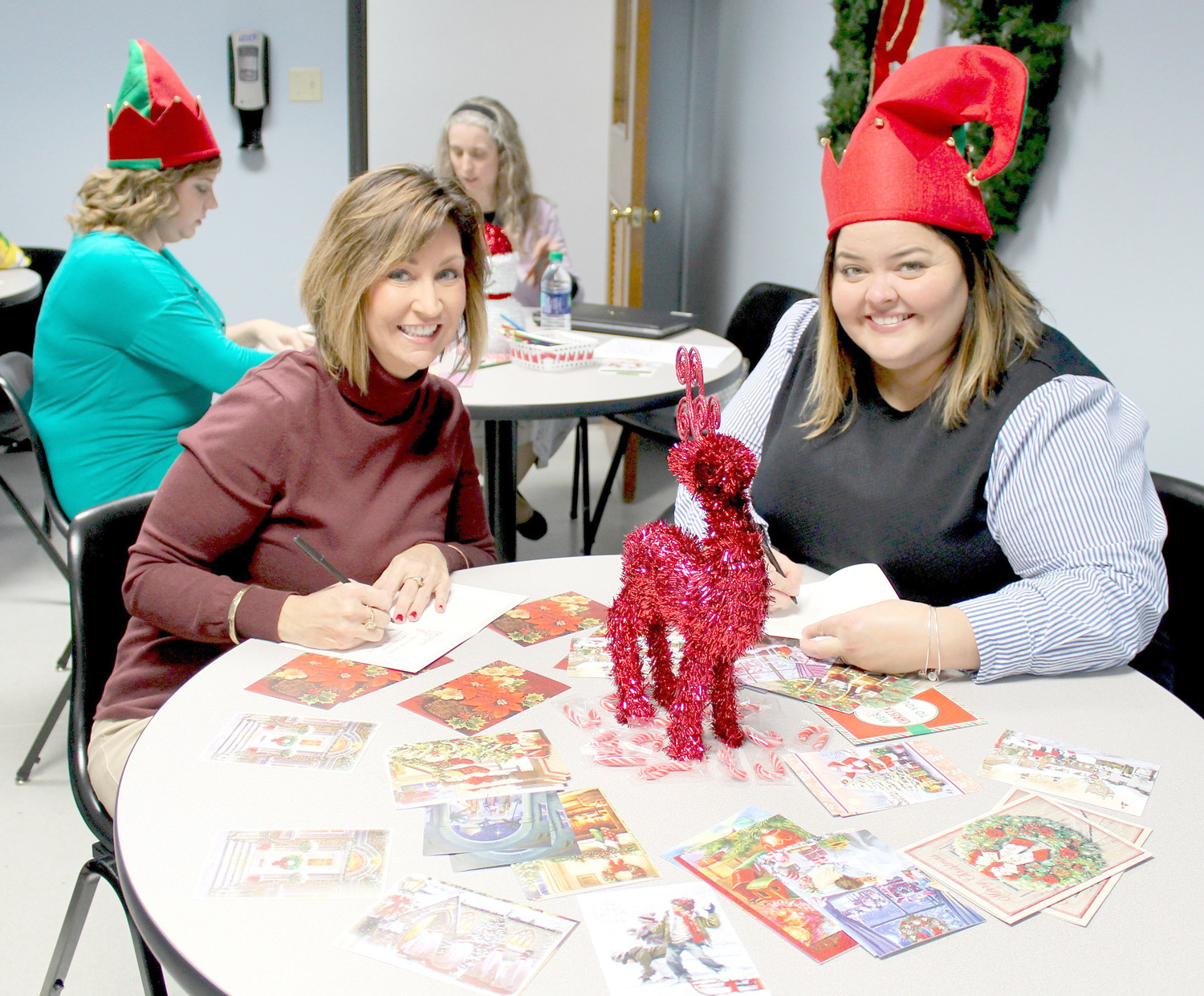 "WHIRLPOOL Customer eXperience Center employees Patti Bowerman, left, and Shannon Russo prepare cards for the American Red Cross' ""Holidays for Heroes"" initiative."