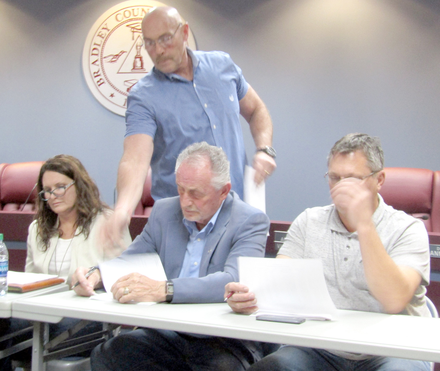 BRADLEY COUNTY Commissioner Dan Rawls hands out a list of what he said were back taxes owed by contractor Mike Crittenden after the commission voted to reimburse Crittenden for work he says he should not have been required to do on his subdivision. Seated, from left, are commissioners Charlotte Peak, Howard Thompson and Bobby Goins.