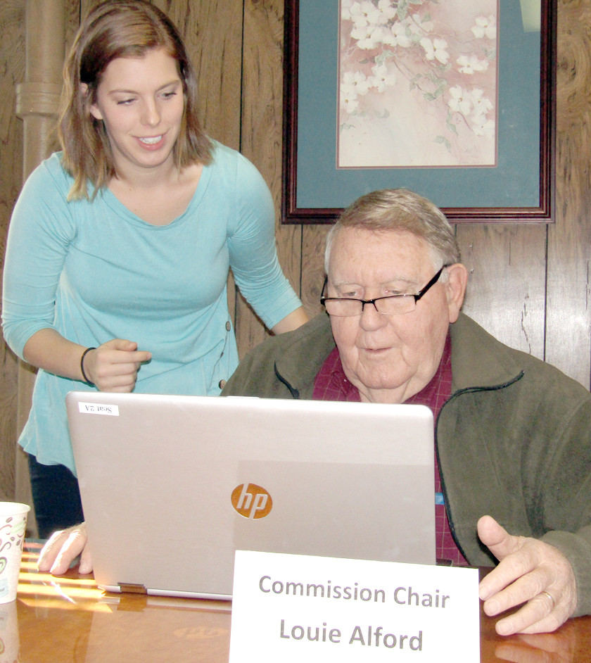 BRADLEY COUNTY Commission intern Rachel Burgess helps commission Chairman Louie Alford with the new laptops the governing body is beginning to utilize in order to cut down on paper usage. Monday's Finance Committee meeting was the second session the laptops have been used.