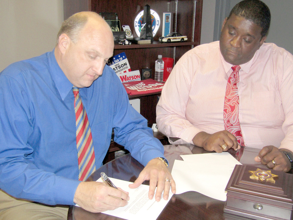 SHERIFF Eric Watson, left, signs the state audit which showed no findings for the fiscal year ending in June. Looking on is BCSO Communications Director James Bradford.