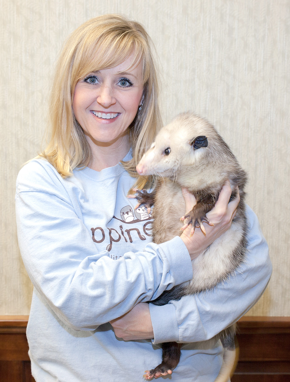 Sherry Teas poses with Eugene, a friendly rehabilitated opossum who was injured as a baby.