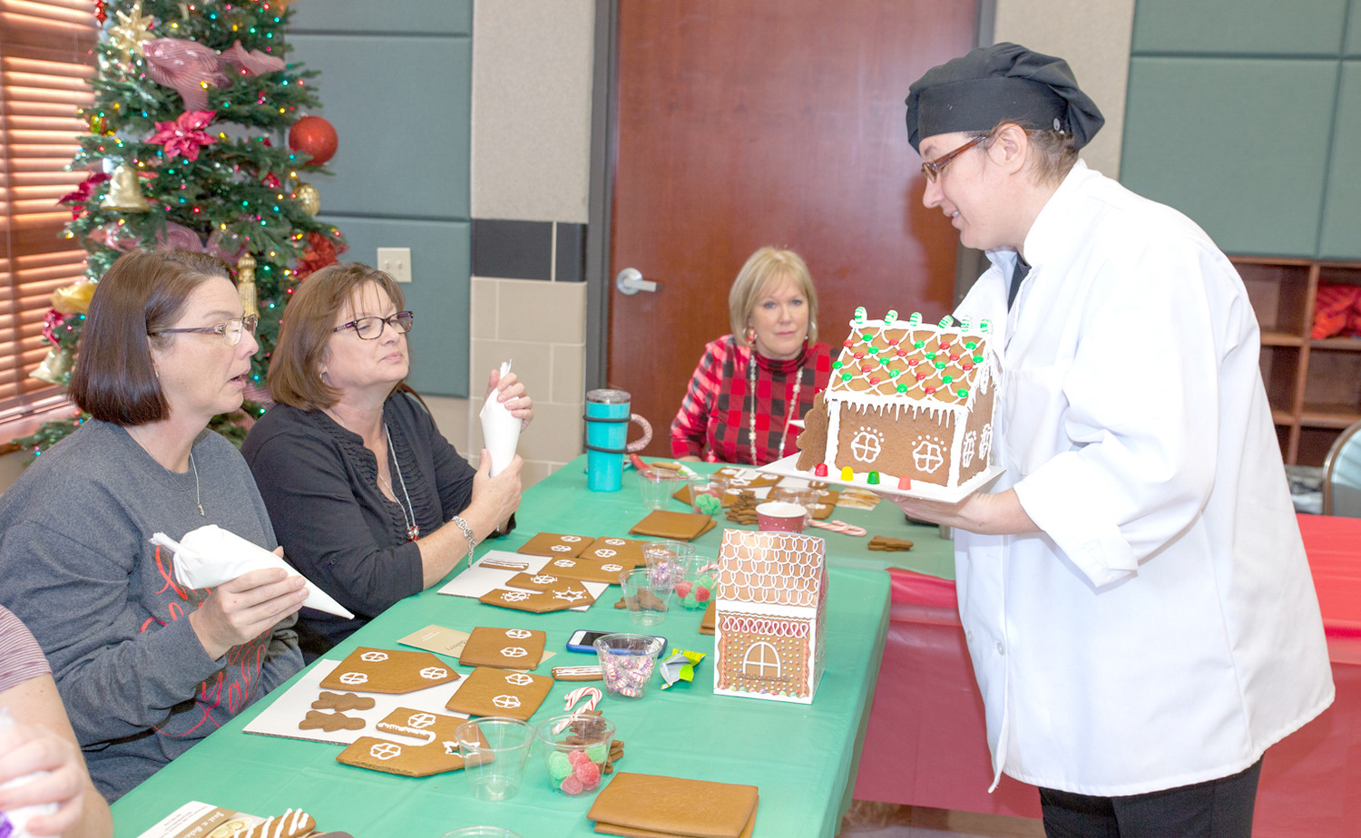MARINA SEPENUK, right, shows some of the students attending the Gingerbread House Workshop the detail on her example house.