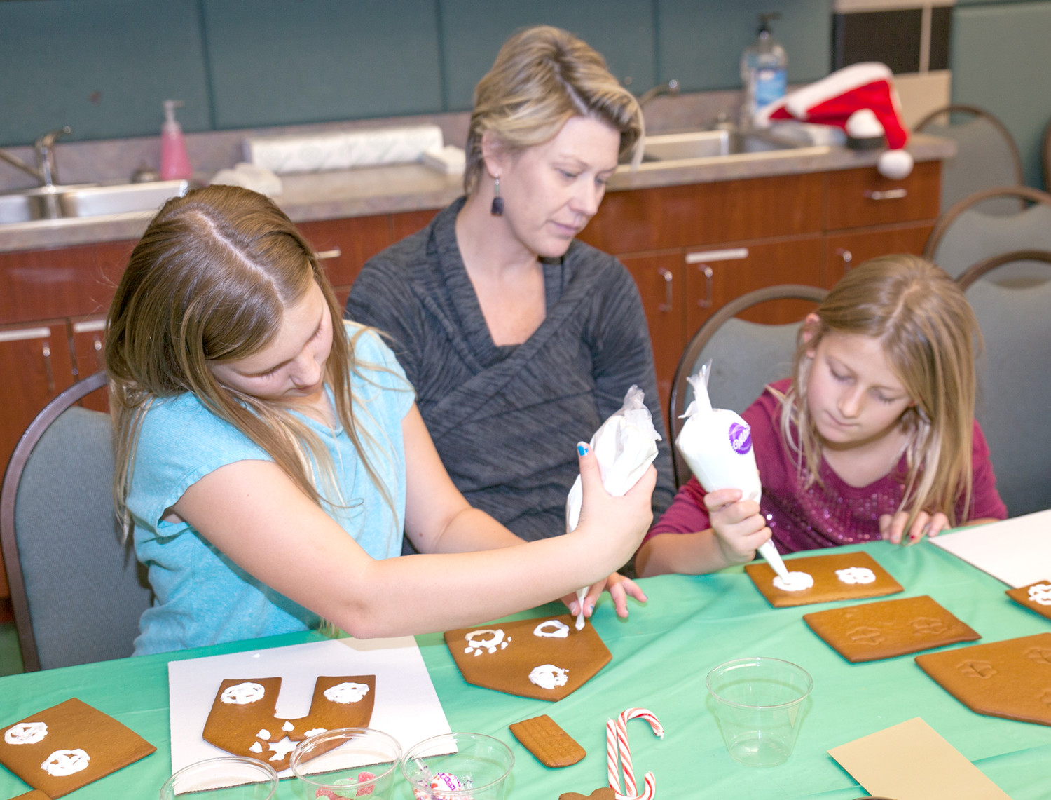 PEARSON, KEY AND TRUE WALLER enjoy the Gingerbread House Workshop at the Christmas Open House and Artist Showcase at the Museum Center at Five Points on Sunday.