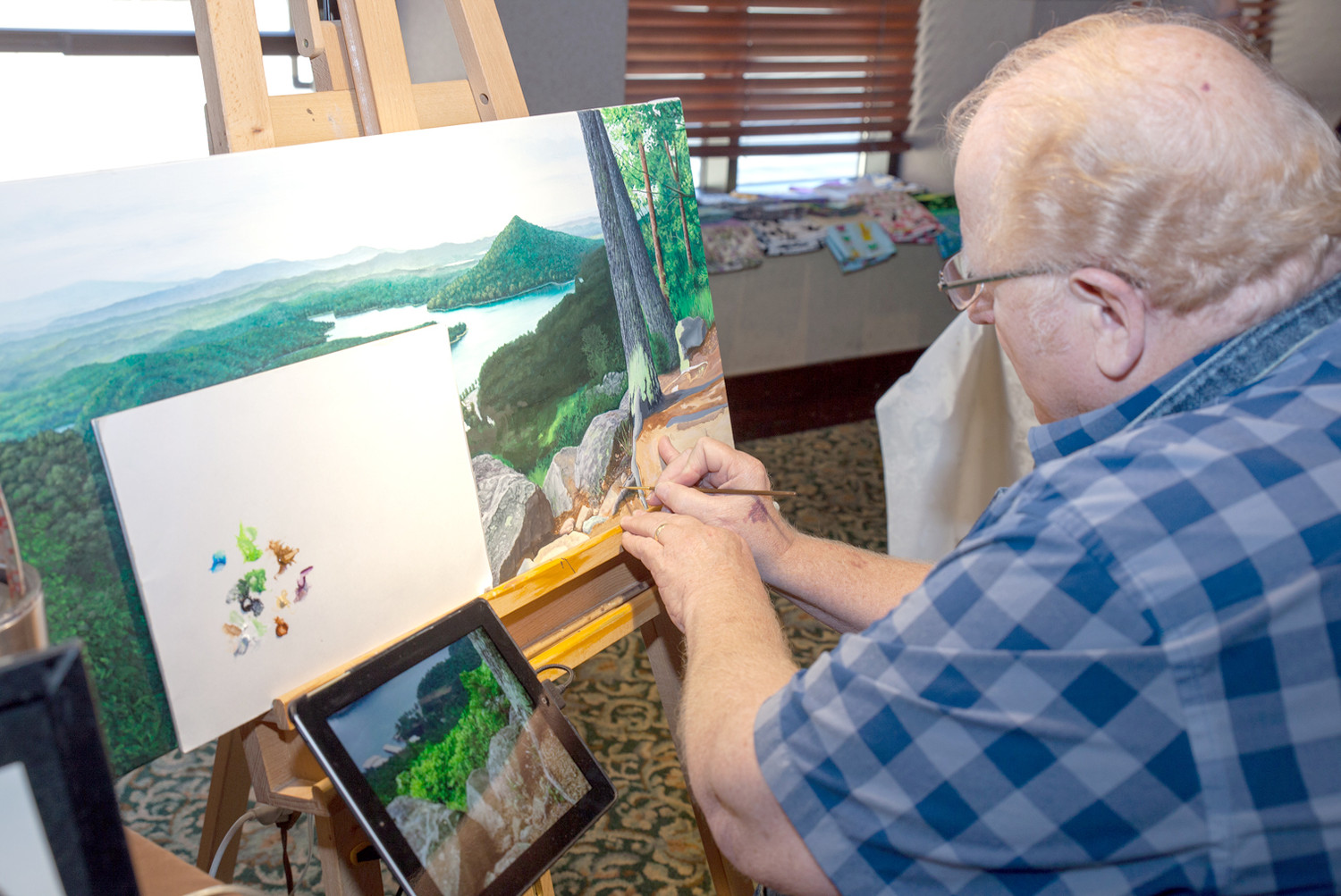 ONE OF THE EXHIBITING artists at the Artist Showcase portion of the event at the Museum was Mike Ivey, right, of Mike Ivey Art. He was working on a landscape during the show on Sunday.