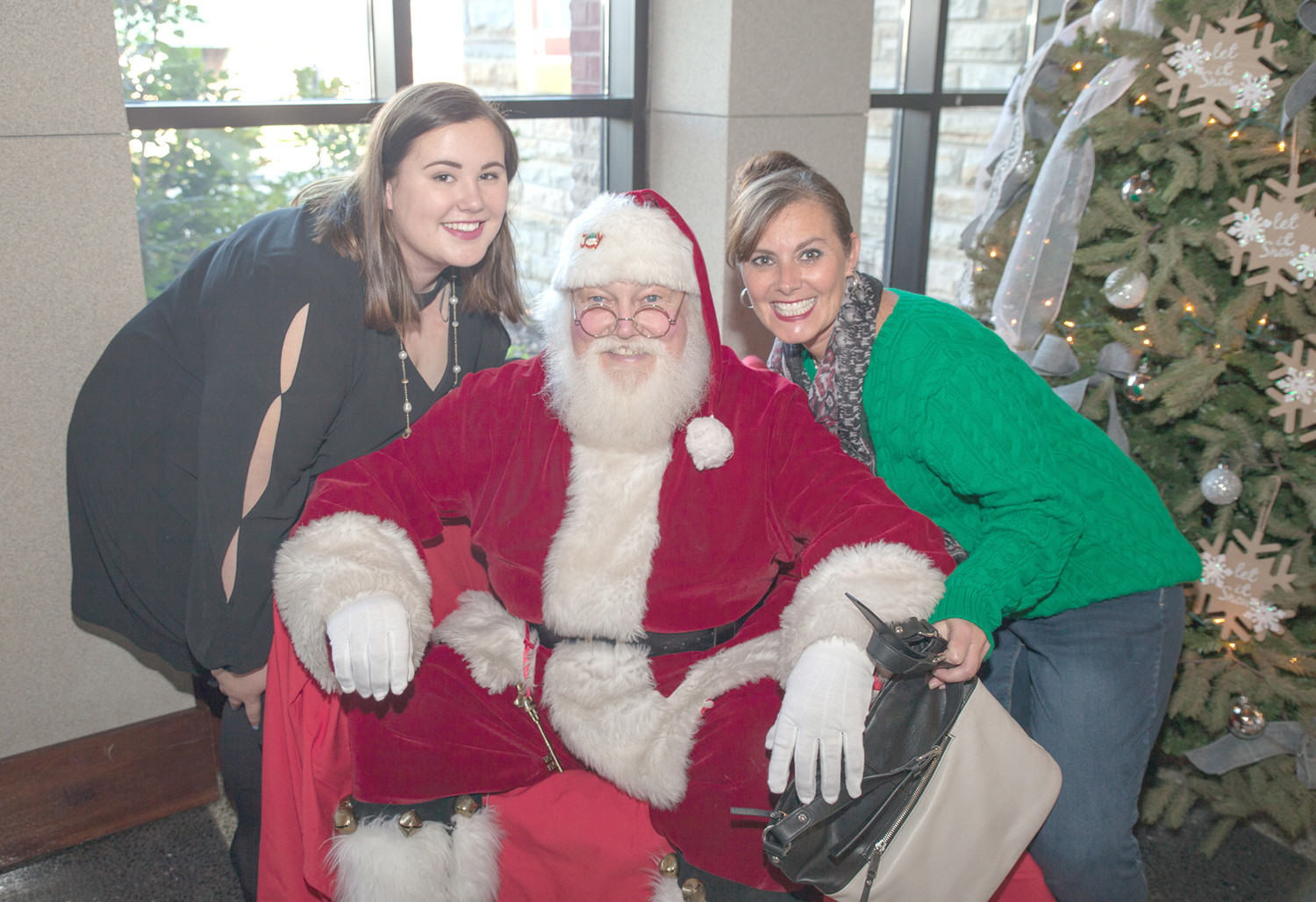SANTA EVEN TOOK SOME time out of his busy December to support the work of local arts and crafts.  Maranda Dye, left, Santa and Virlena Dye, right, pose with Santa during the event.
