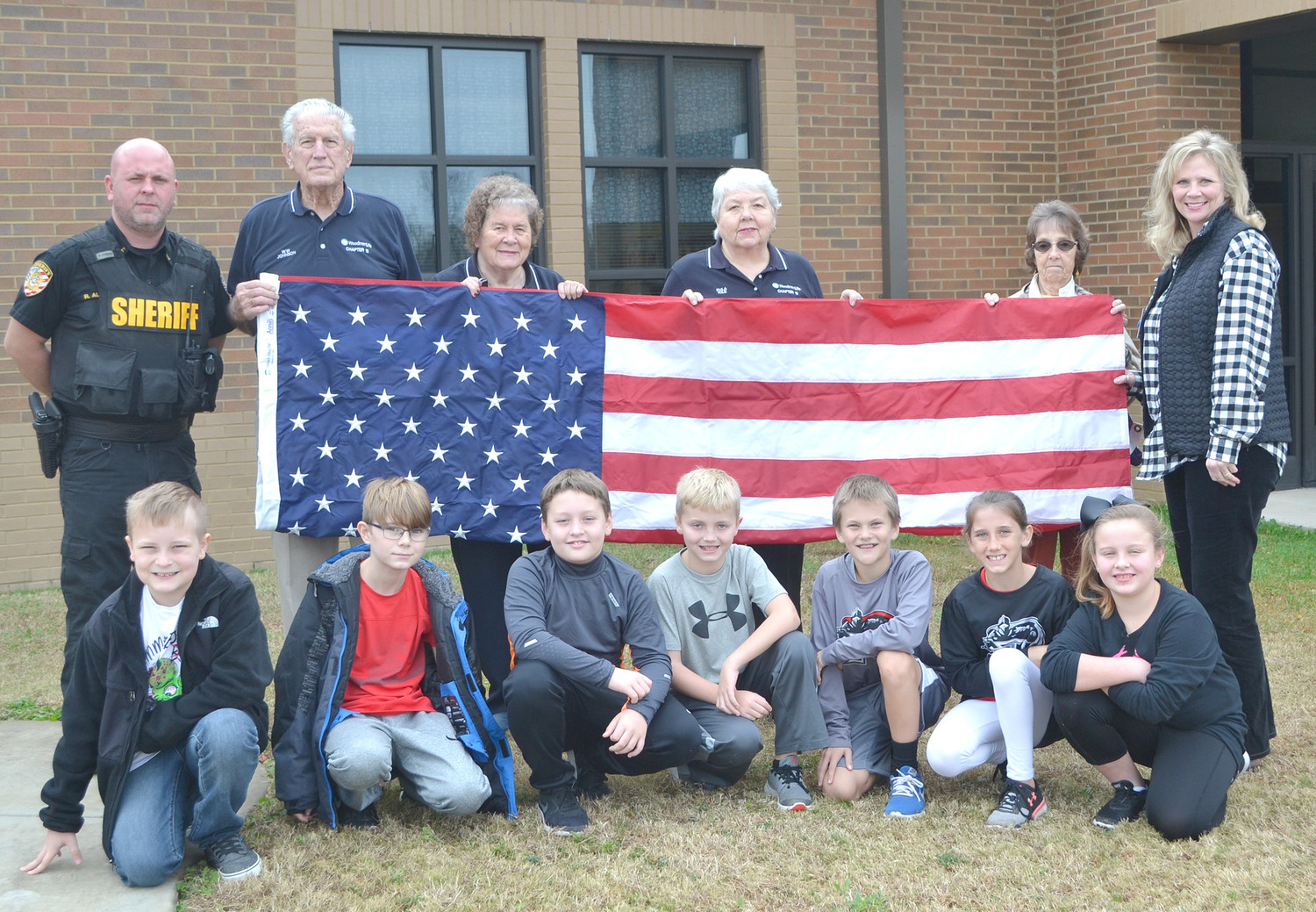 WOODMEN LIFE recently presented a U.S. flag to Park View Elementary. From left front are school patrol members Riley Crittenden, Jace Maples, Tate Rountree, Knox Gatlin, Drake Morrow, Alyssa Davenport and Lynlee Hodge. In back are Richard Allman, W.W. Johnson, Joyce Johnson, Eula Lake, Christine Miller and Jodie Grannan.