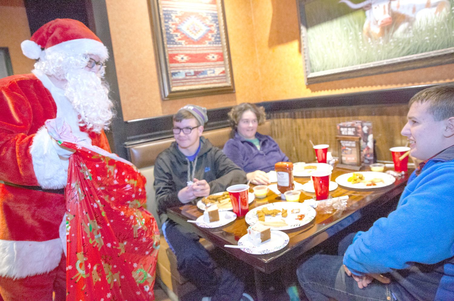 SANTA CLAUS made a surprise visit at LongHorn Steakhouse on Friday to cap off the wonderful meal that the children from the CHS special services department enjoyed.  Santa passed out candy to each and every table during his visit.  Pictured from left are Santa, Luke, Adeline and Connor.