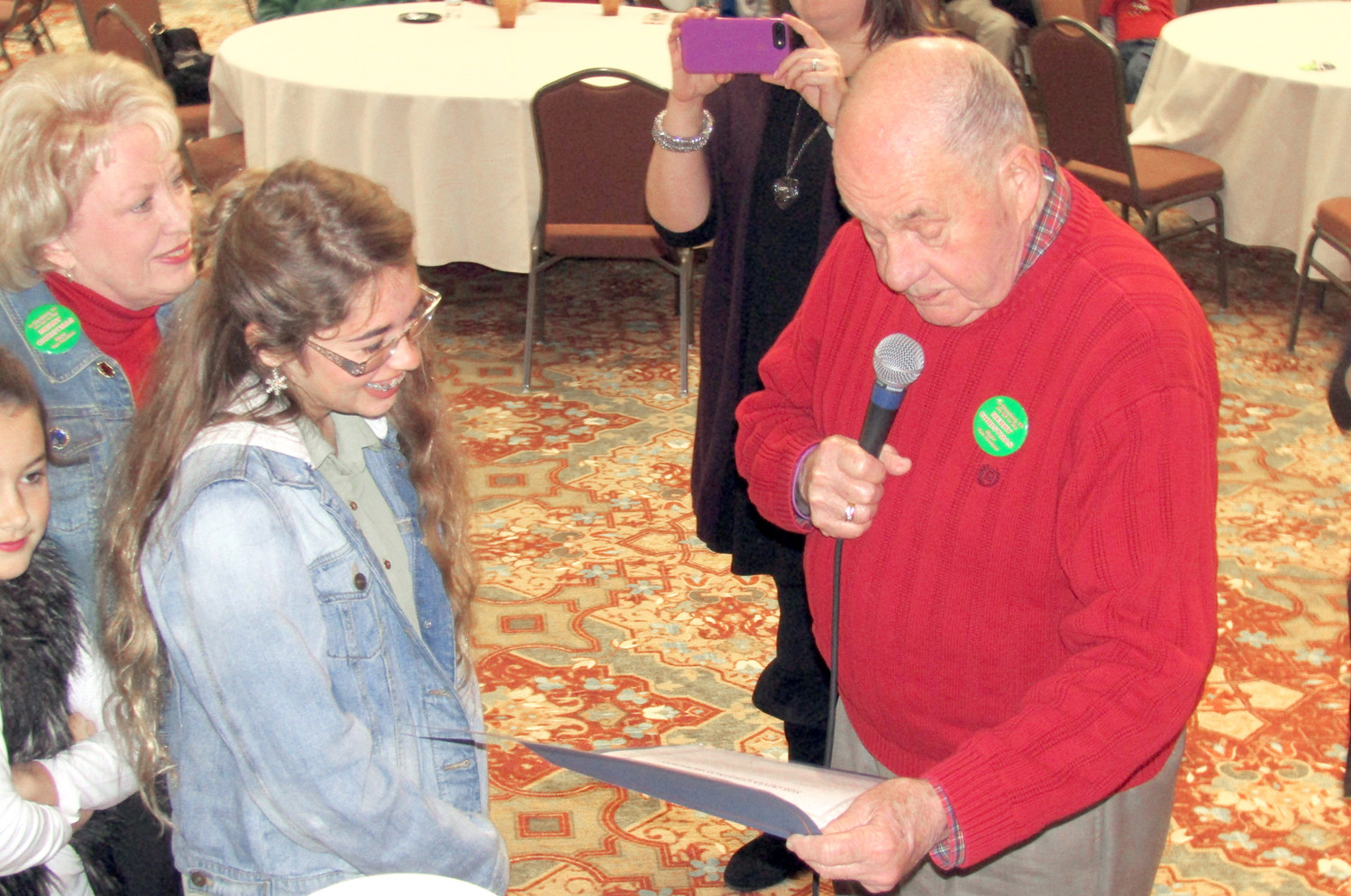 Mayor Tom Rowland, right, presents Olivia Christmas Workman with a certificate making her Mayor for a Day as a result of a special drawing during the Empty Stocking Fund drive. At left is first lady Sandra Rowland.