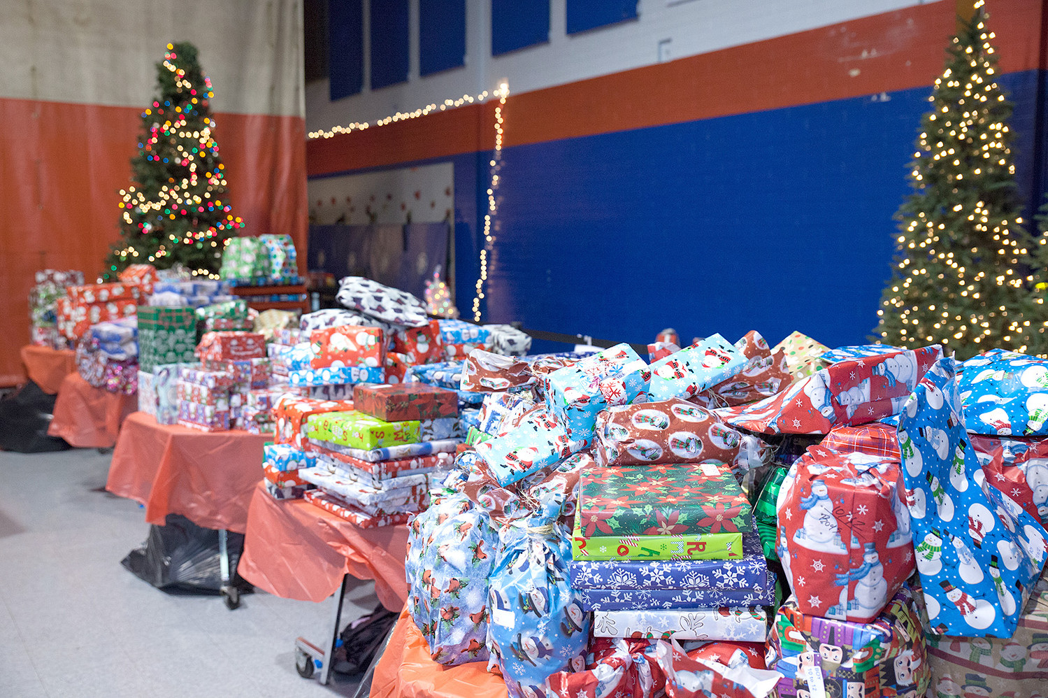 MOUNTAINS OF PRESENTS awaited each child after the activities and food at the Catch the Spirit event.  Each table is separated by age range and gender.