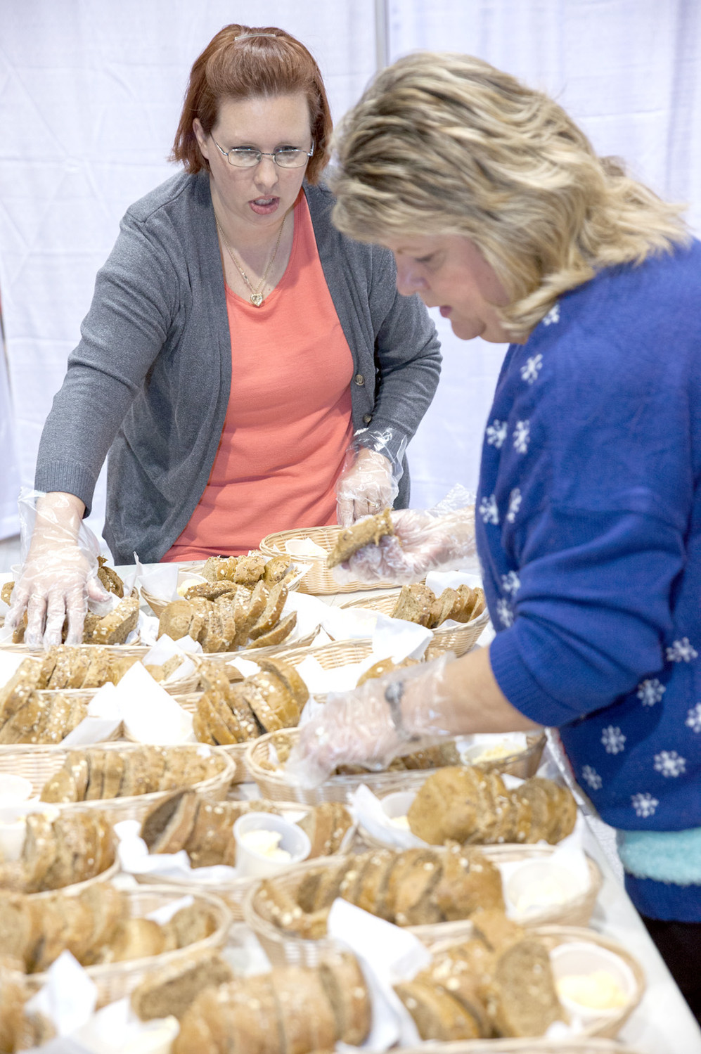 VOLUNTEERS Tonya Young, left, and Pam Stone prepare the bread baskets that are to be placed on each dining table for event attendees to enjoy with their meal.