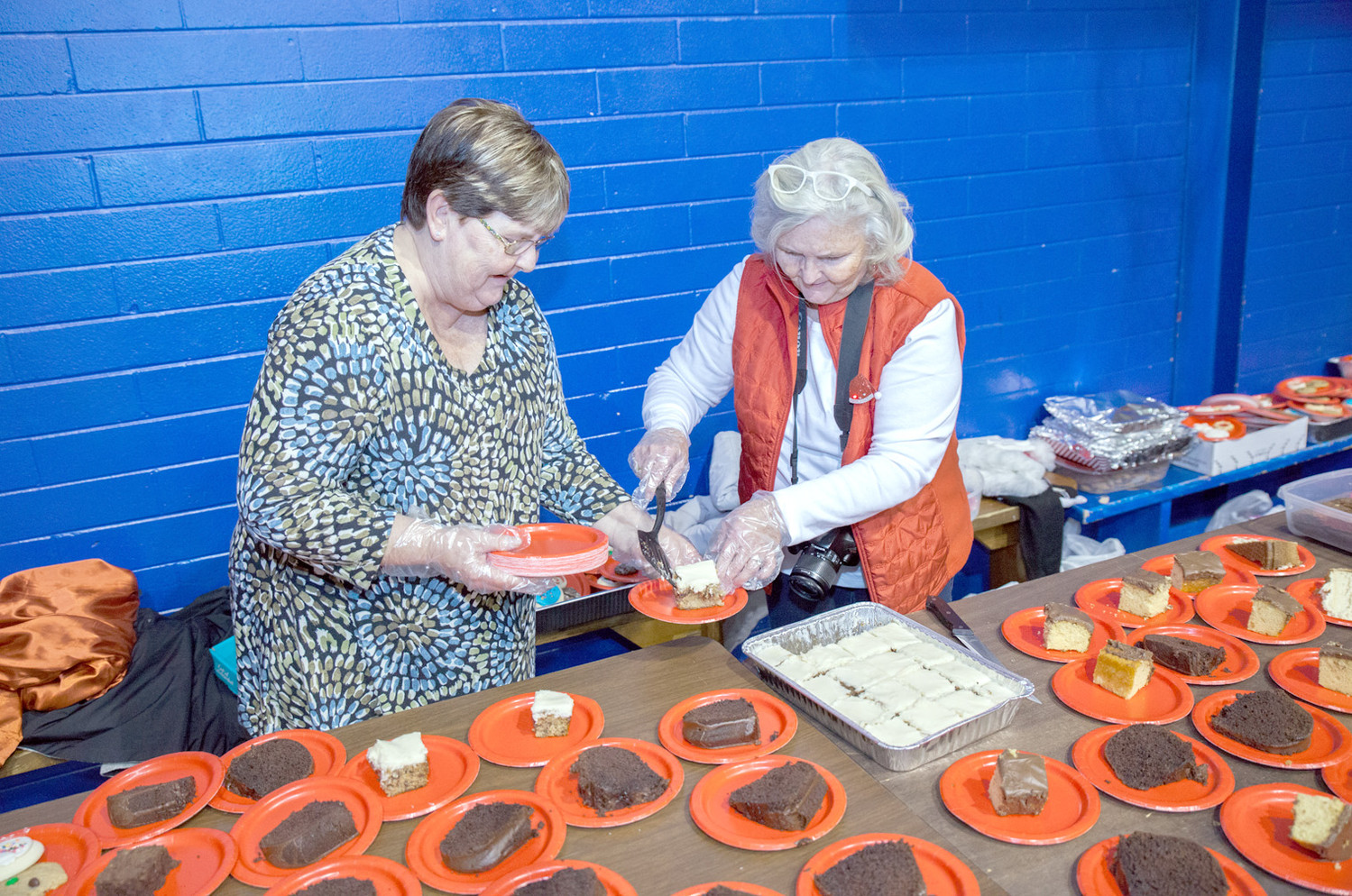 VOLUNTEERS Rhonda Jones, left, and Gerri Rominger prepare the sweet dessert table servers will visit to fulfill their table's orders.
