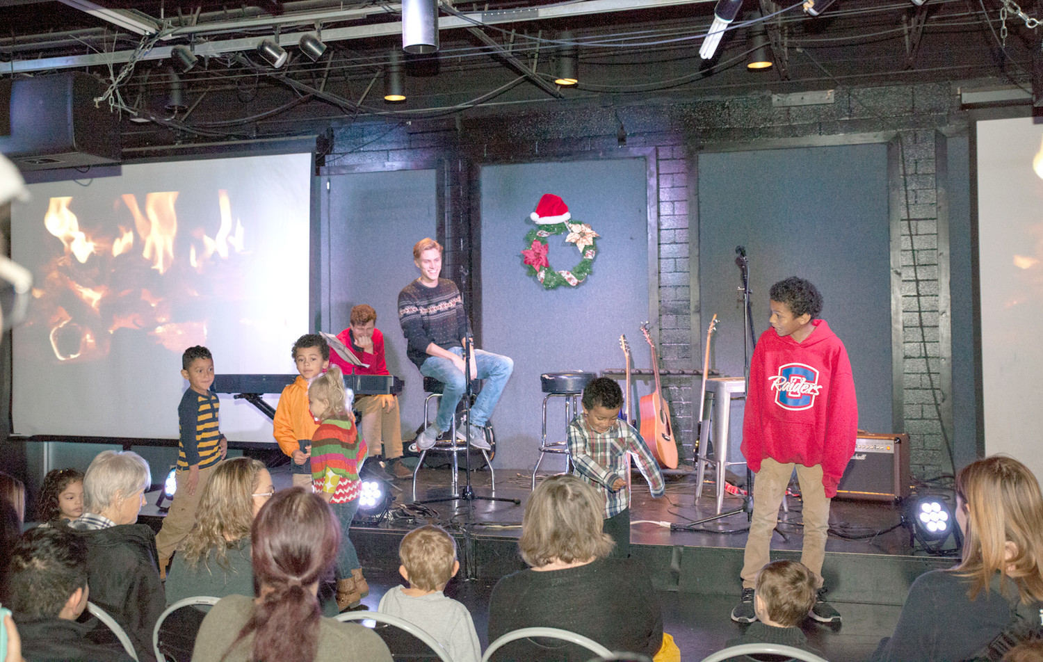 IN THE PERFORMING ARTS room, volunteers Jonathan Cox, back left, and Jesse Miller, center, look on as some children chosen from the crowd participate in a dance-off.  Attendees were treated to singing, dancing, jokes and games prior to their meal at the Catch the Spirit event.