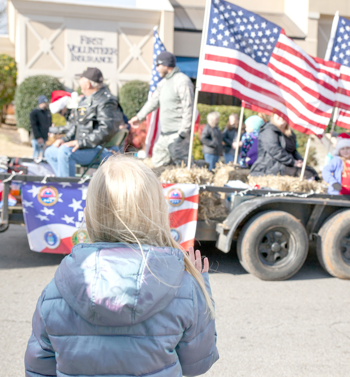 A LITTLE GIRL waves at the passing AMVETS parade float on Saturday, Dec. 9, 2017.