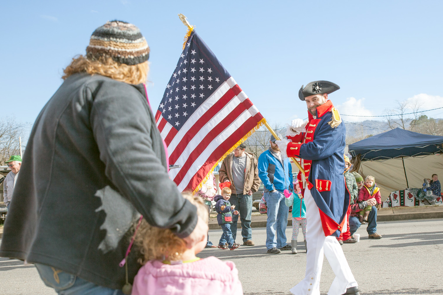 A FLAG BEARER waves to a family during the Polk County Parade.