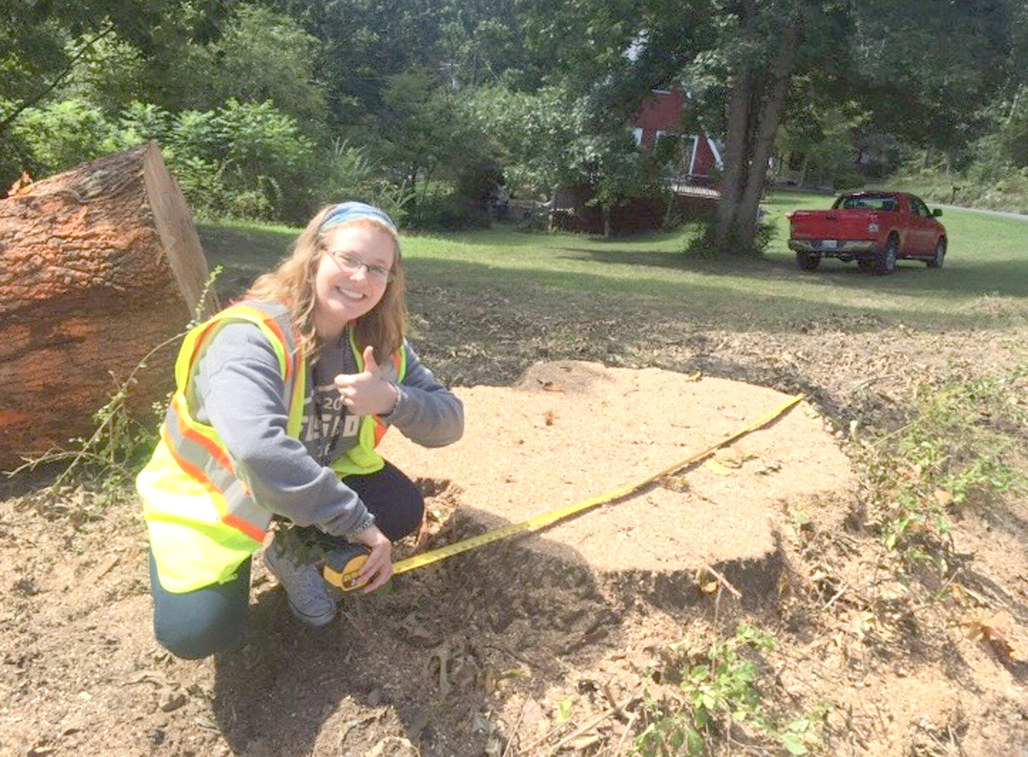 EMILY HARRIS MEASURES a tree stump while interning at Bradley County Road Department.
