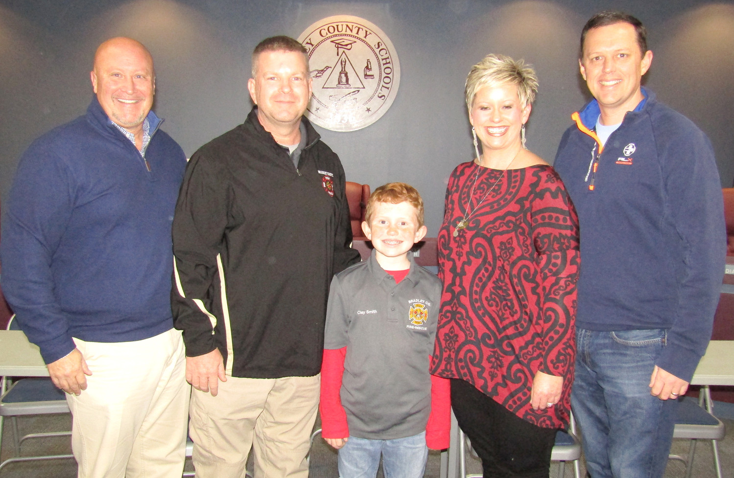 CLAY SMITH, center, a student at Michigan Avenue Elementary School, served as 'Fire Chief for a Day' with the Bradley County EMS. Standing with him are, from left, EMS Committee Chairman Commissioner Johnny Mull, EMS Director Shawn Fairbanks, Smith, and his parents, Rachelle and Spencer Smith.
