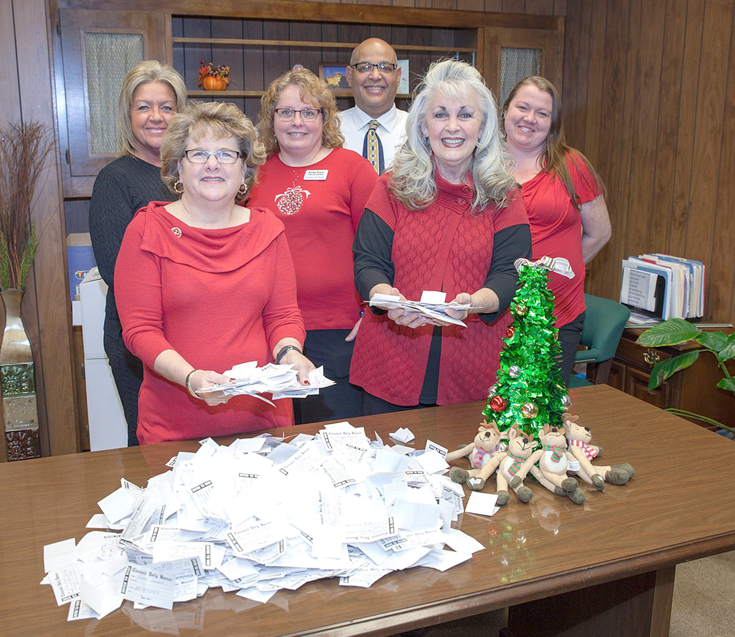 CLEVELAND DAILY BANNER sales representatives look at all the entries in the Catch the Holiday Spirit Banner Bucks promotion. From left, front, are Sheena Meyer, sales director; Kathy Payne, Leslie Callaway, back, Pam Green, Randy Moore and Tasha Beaty. The winner of the $500 in Banner Bucks was selected Wednesday.