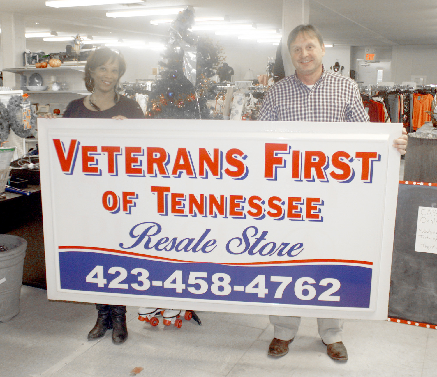 GRANT PIRKLE, right, president of Veterans First of Tennessee Resale Store, joins store manager Sonya Locklin in displaying a sign for the organization's new location on South Lee Highway.