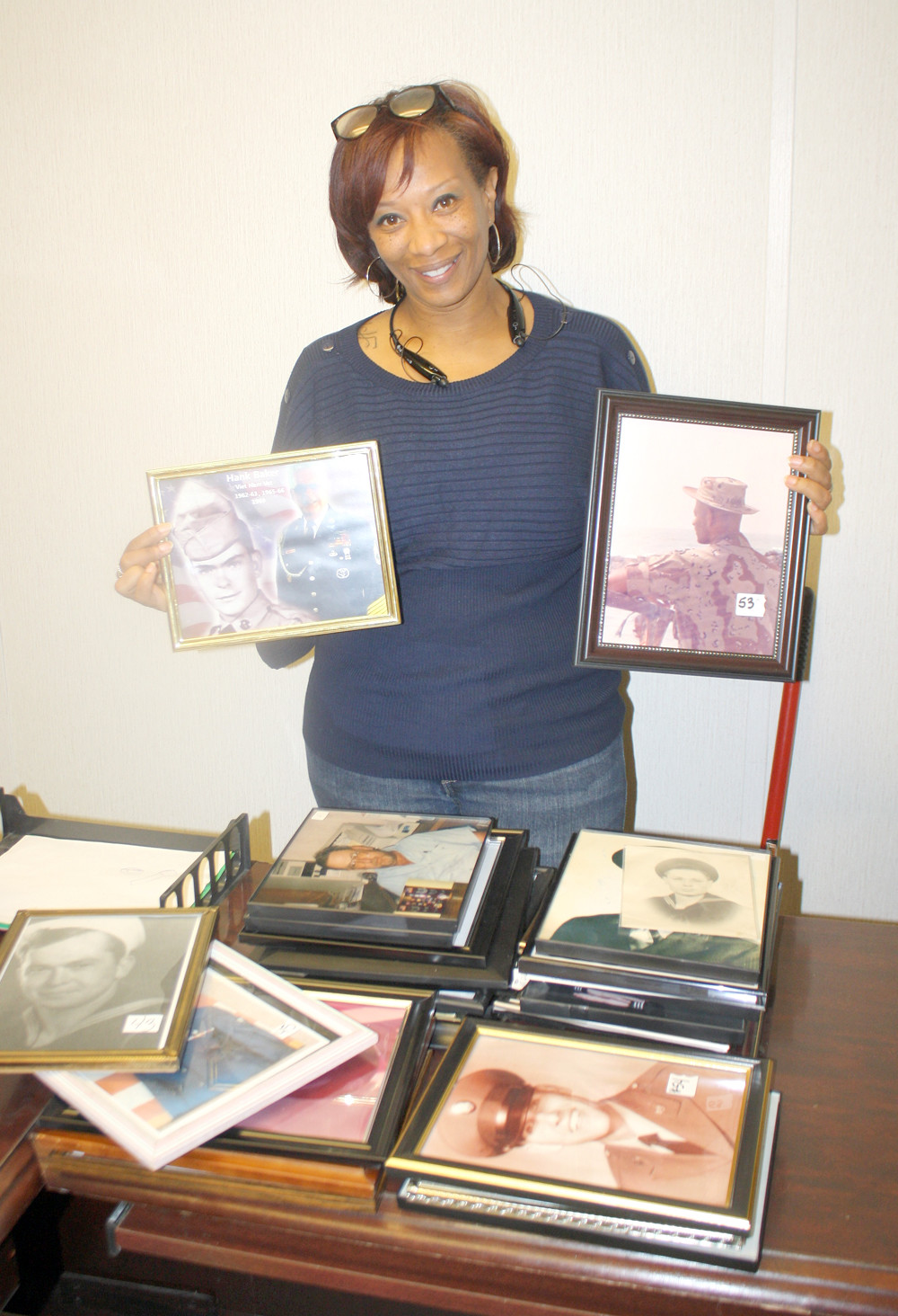 SONYA LOCKLIN, manager of the Veterans First Resale Store on South Lee Highway, shows a few photographs of veterans to be displayed on a store wall.