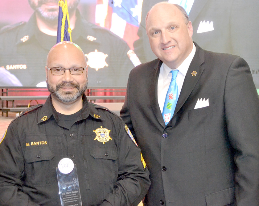 SGT. MARIO SANTOS, left, was honored at Thursday's Bradley County Sheriff's Office Christmas dinner as Supervisor of the Year. Making the presentation is Sheriff's Eric Watson.