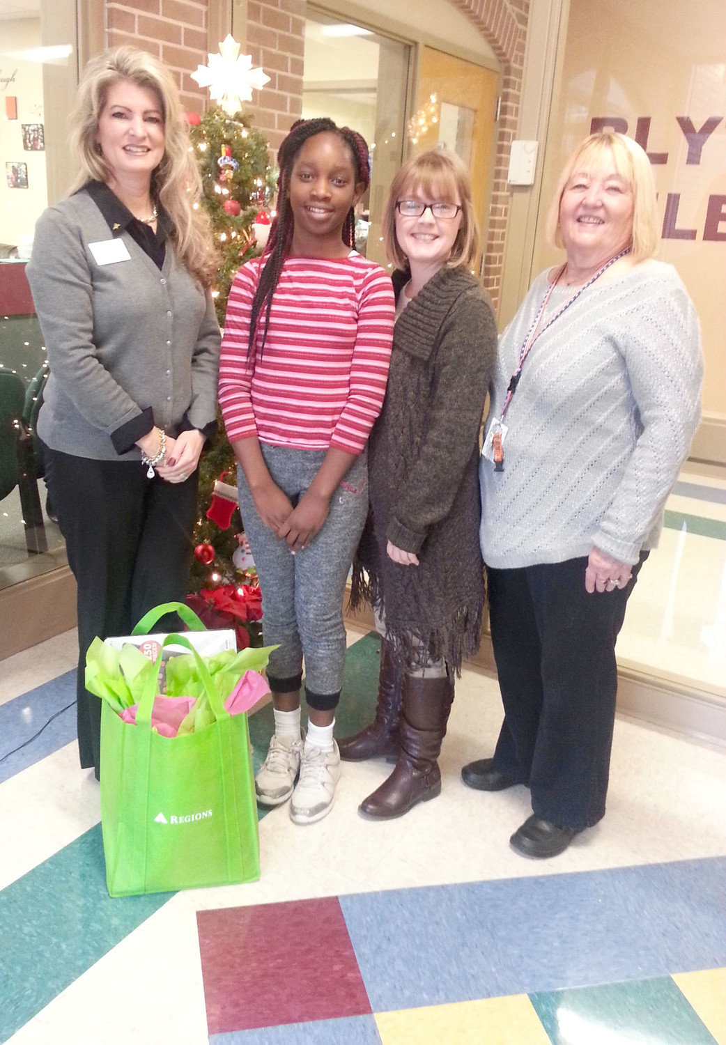 Regions sponsored a Holiday Card Contest with BEST Partner Blythe-Bower Elementary School. Gathered are Lee Loveridge, Regions Bank; fifth-grade student winner Allanah Hinkson; Nicki Johnson, Blythe-Bower teacher; and Linda Tyler, family engagement coordinator.