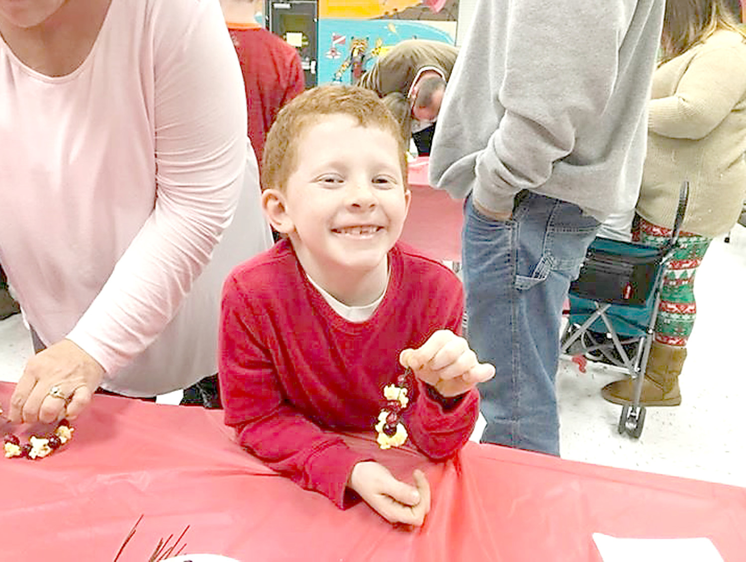 BRAYDEN SMITH proudly displays the ornament he made using popcorn and cranberries, during Hopewell Elementary School's Country Christmas.