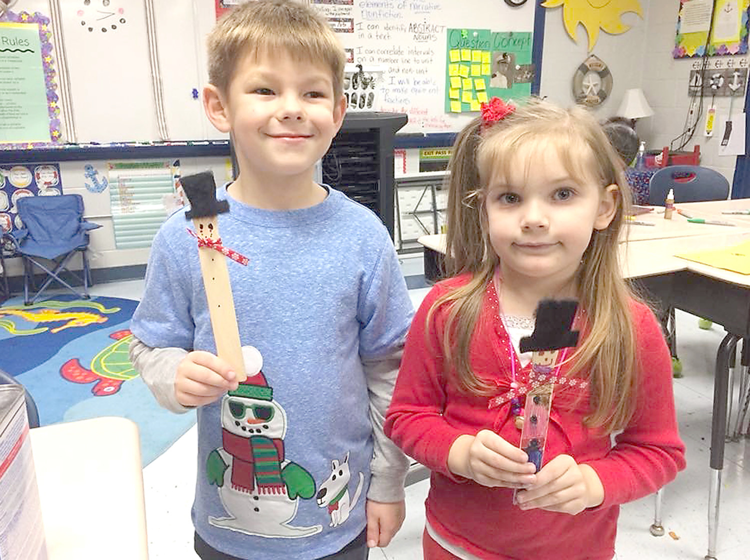 LILLI LEAMON and Bryson Cannon show off the paint stick snowmen they made during the annual Country Christmas event at Hopewell Elementary School.