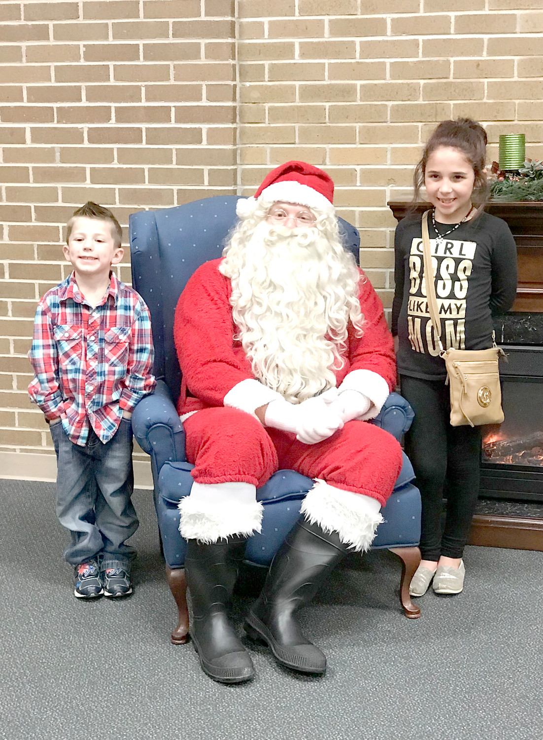 SANTA CLAUS visits with two happy students during the Christmas Dance and Fun Night event at Blythe-Bower Elementary School.