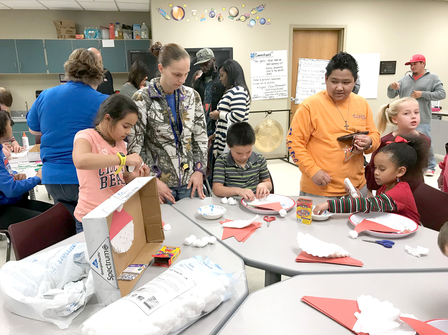 PARENTS AND STUDENTS work together to make some Santa Claus-themed Christmas crafts during Blythe-Bower Elementary's  Christmas Dance and Fun Night.