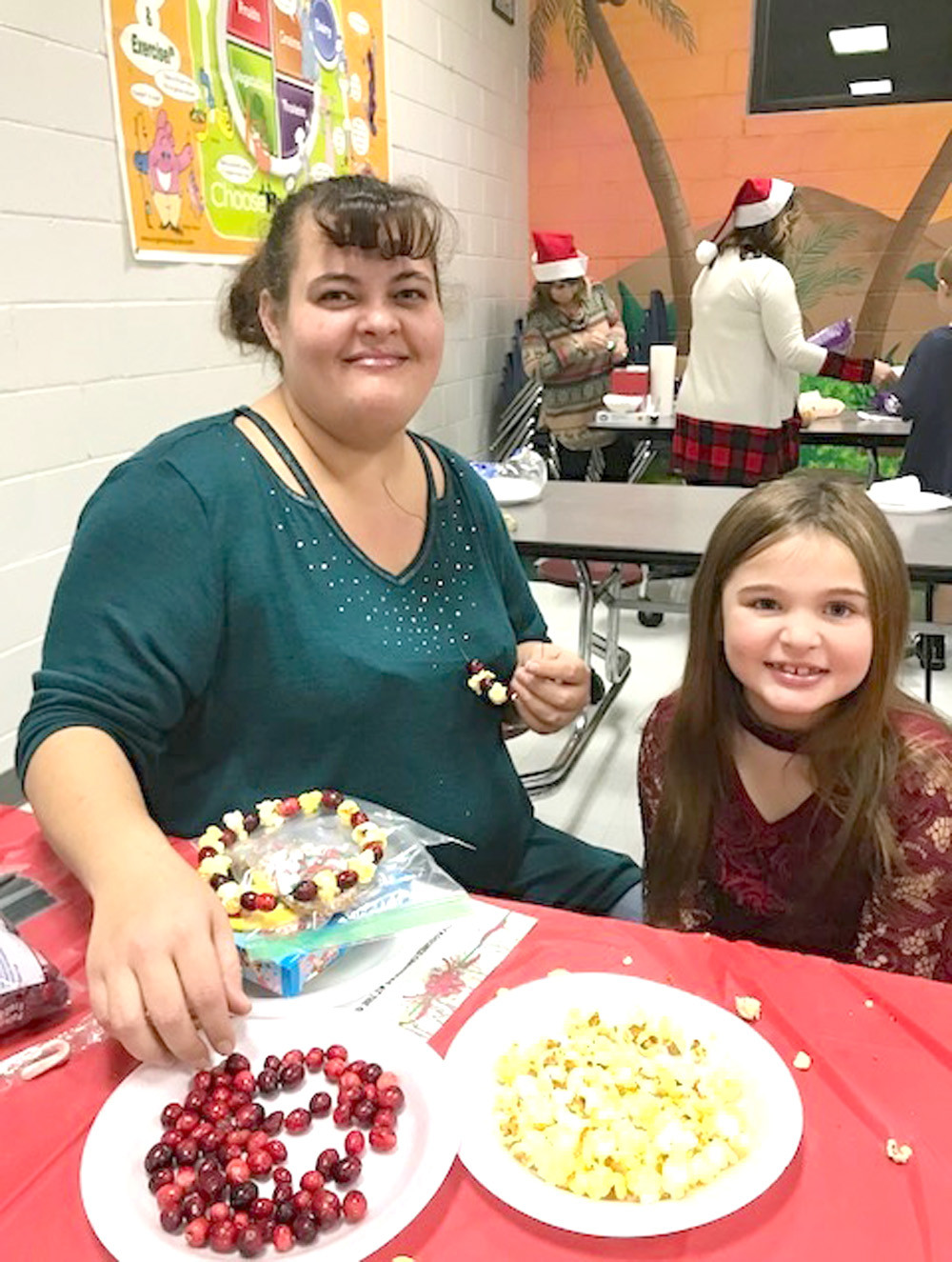 "KATELYNN BOONE and her mom string popcorn and cranberries during Oak Grove Elementary's ""Old Fashioned Christmas at the Grove."""
