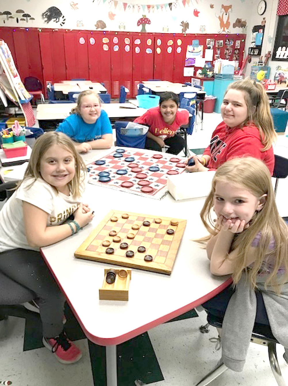 STUDENTS Jazlyn Murray, Kaitlyn Ledford, Aubrey Ledford, Brooke Wooten and Ana Elizondo play checkers during Oak Grove Elementary's Christmas event.