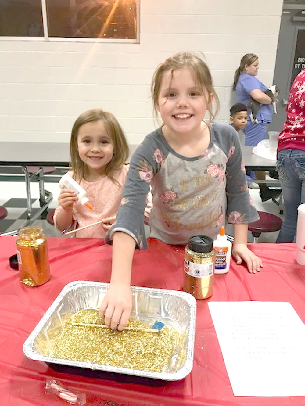 "BELLA AND SELENA RITCHEY make ornaments to take home during ""Old Fashioned Christmas at the Grove,"" held recently at Oak Grove Elementary."