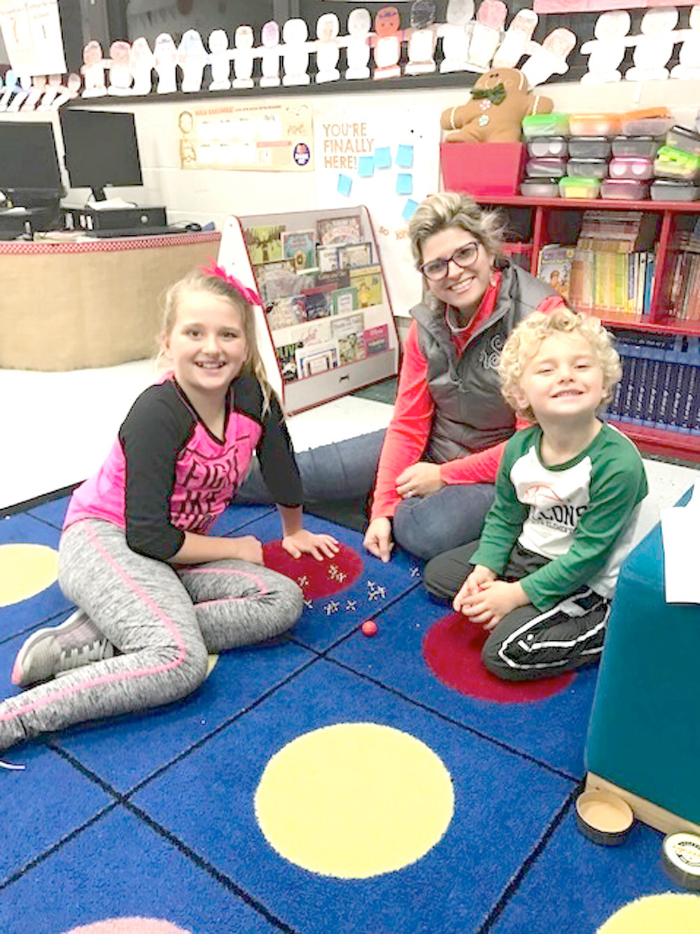 "PRESLEIGH SANDERS was joined by her mom and brother at ""Old Fashioned Christmas at the Grove."" Here, they are playing a game of jacks."