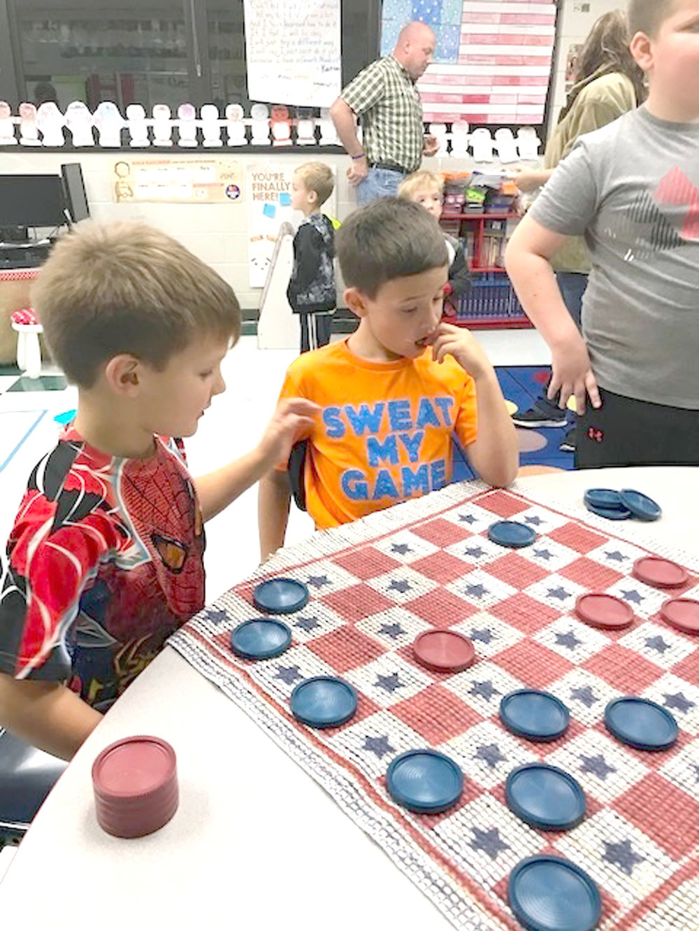 "GAVIN AND RACE JUDKINS play a game of checkers during Oak Grove Elementary's ""Old Fashioned Christmas at the Grove."""