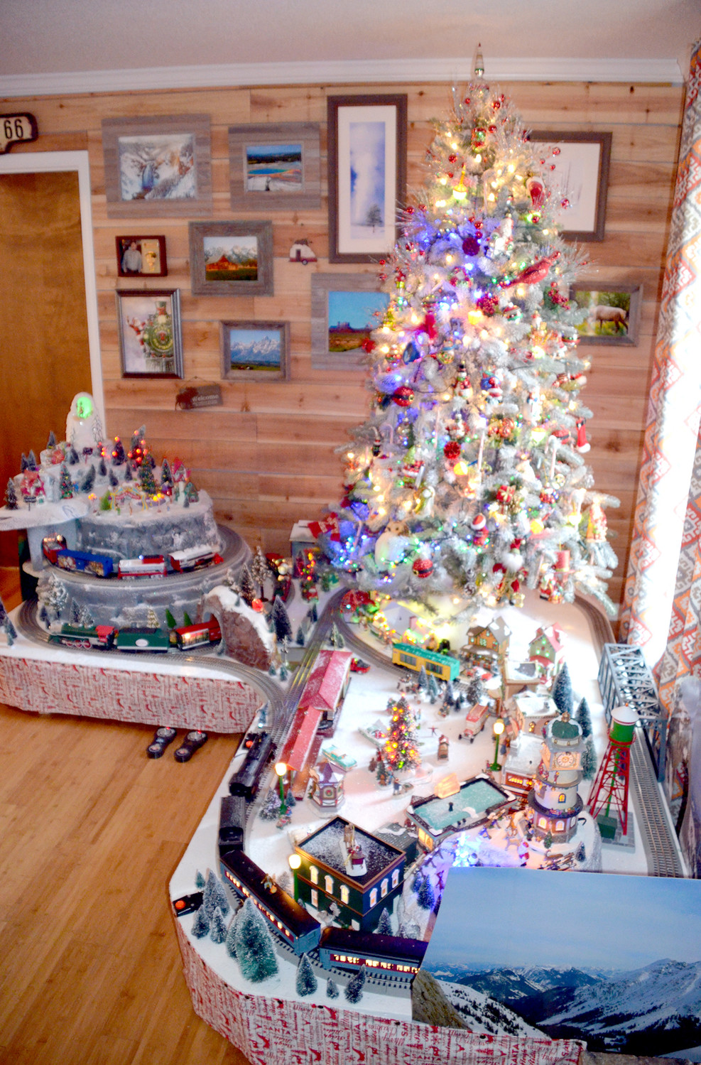 THREE LIONEL TRAINS traverse over mountains, bridges and under the massive Christmas tree in the Baynes family living room.