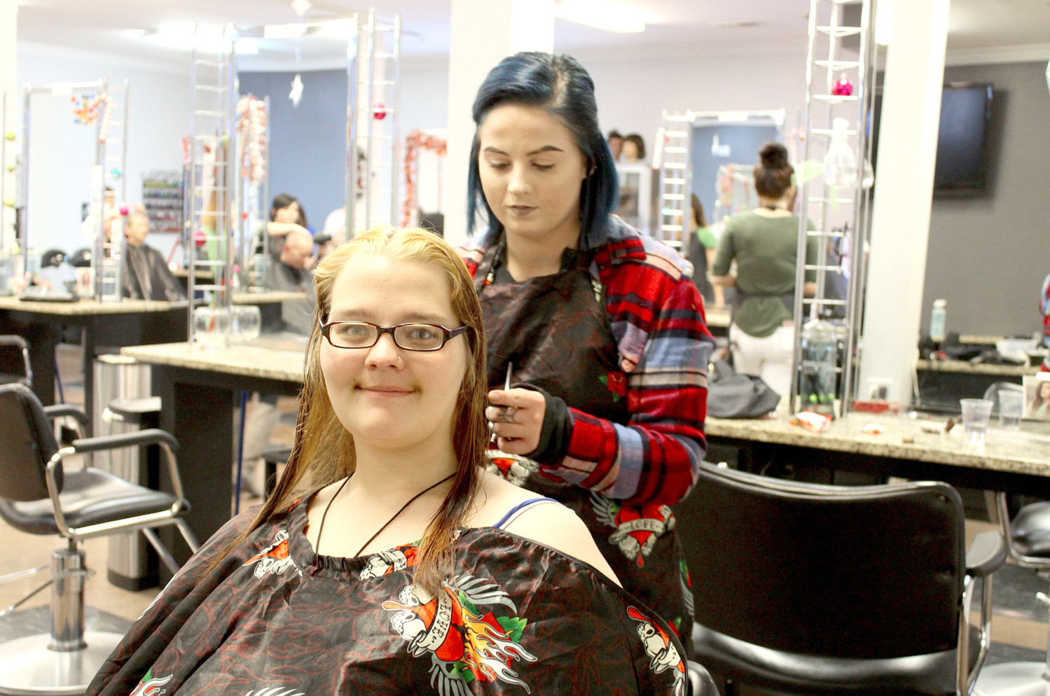 "JANET GRYDER smiles as she receives a new haircut from Franklin Academy student Alexan Crittenden during the school's event to ""pay it forward"" the community. 