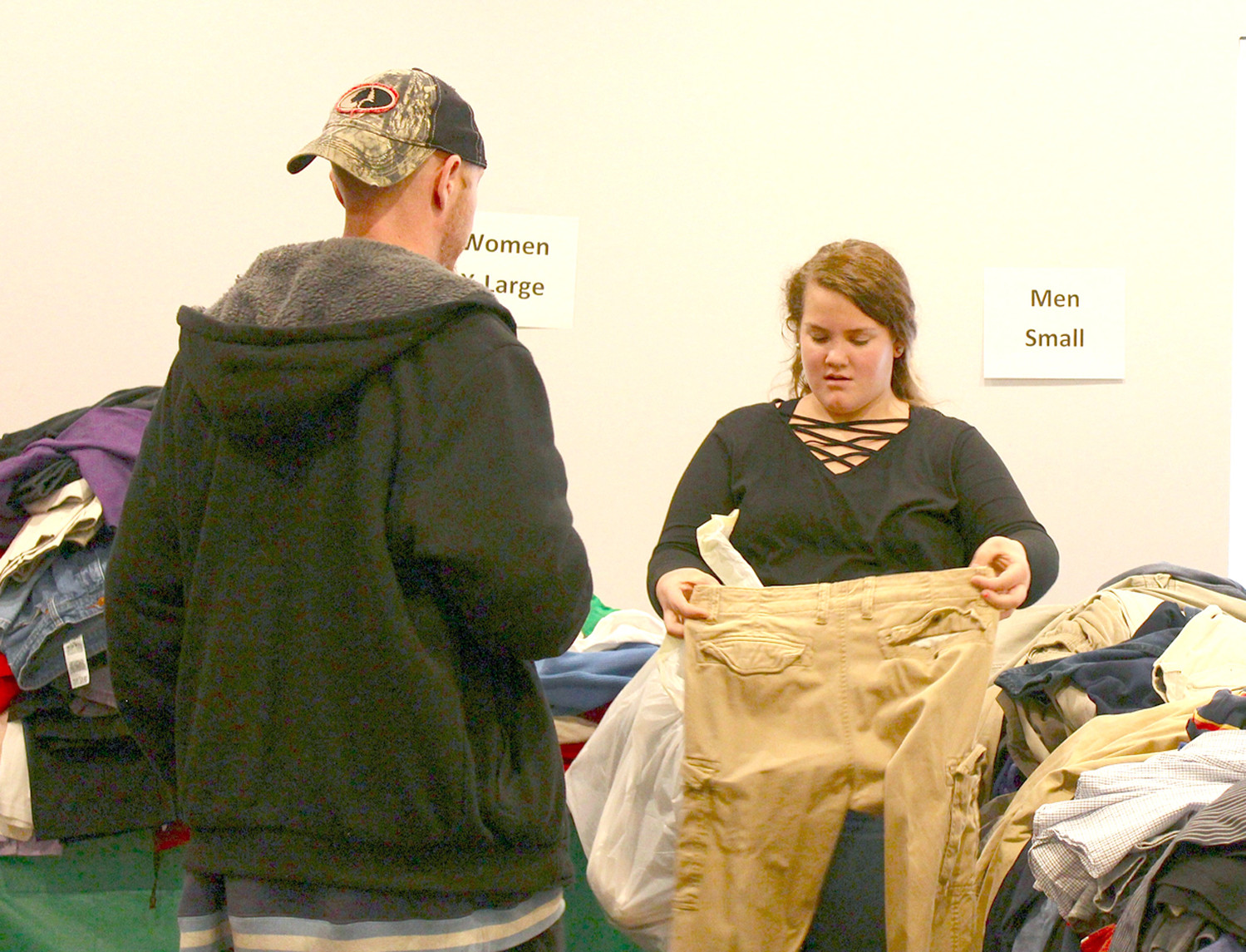 OLUNTEER Ariana Curtis helps a gentleman find pants in his size during a recent charity event at Franklin Academy. Chattanooga Goodwill Industries donated 1,200 pounds of clothing, and youth from Family Worship Center helped distribute the clothes.