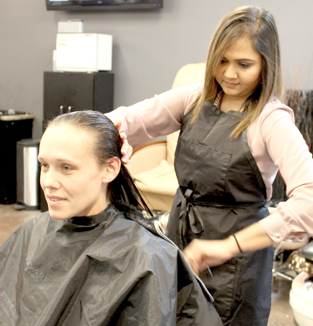 MEREDITH SULLIVAN keeps an eye on things in the mirror as Franklin Academy student Nikita Patel gives her a haircut during the school's recent charity event.